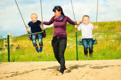Mother and children having fun on a swing outside