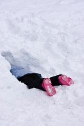Young girl tunneling through a snow bank, Minneapolis, Miinnesota, USA