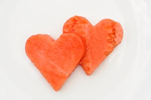 Two heart shapes cut out of a watermelon slice