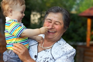 cute grandson grabbing the nose of laughing great grandmother. f