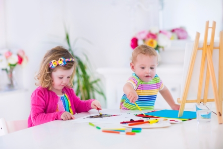 Children paiting on wooden easel
