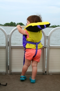 Toddler aged girl wearing a life jacket on a deck boat while on a lake