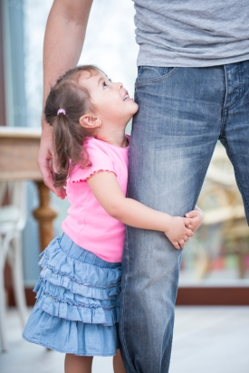 Side view of girl hugging father's leg in house