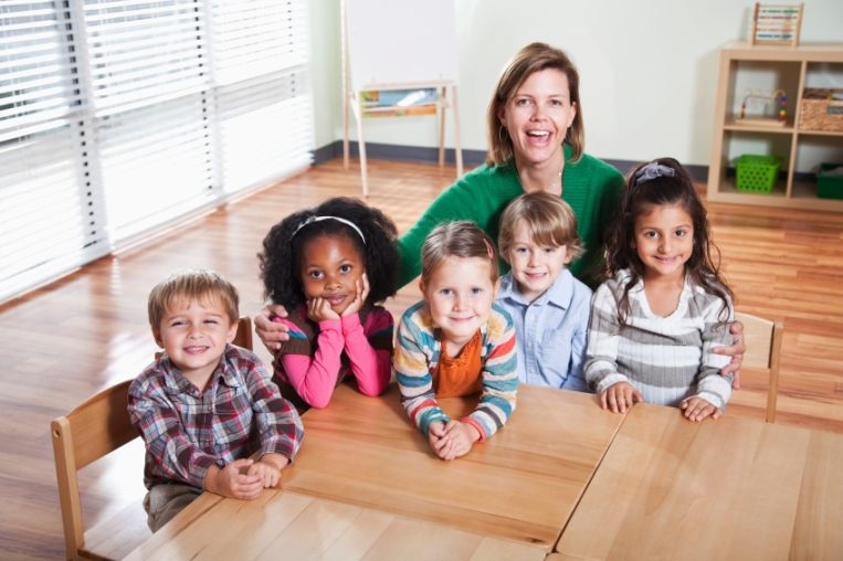 Preschoolers with teacher sitting at table in classroom