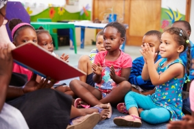 Teacher reading a book with a class of preschool children