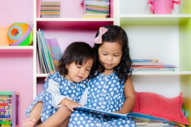 Child read, two cute little girls reading book together on books