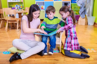 Kindergarten teacher reads a book to children at school