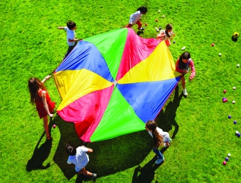Kids going round in a circle with bright parachute
