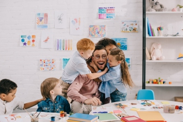 interracial kids hugging happy teacher at table in classroom